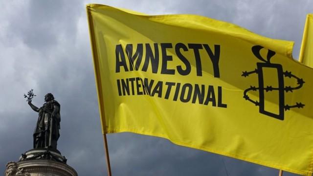 des-manifestants-brandissent-le-drapeau-d-amnesty-international-lors-d-une-manifestation-lors-d-une-manifestation-place-de-la-republique-a-paris-le-5-septembre-2015_5516355-e1494682280904.jpg
